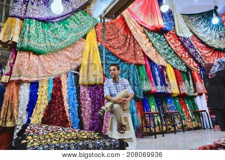 Fars Province Shiraz Iran - 19 april 2017: A lone seller is sitting on a banquet in the textile department of the market.