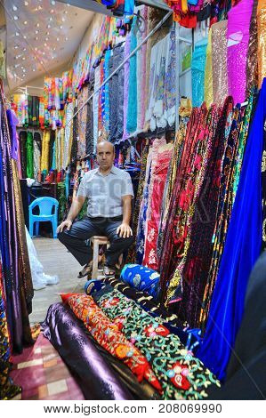 Fars Province Shiraz Iran - 19 april 2017: One unknown Iranian seller sits among bright colorful fabrics in the textile shop of the city bazaar.