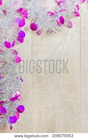 Christmas silvery festive tinsel on a wooden background
