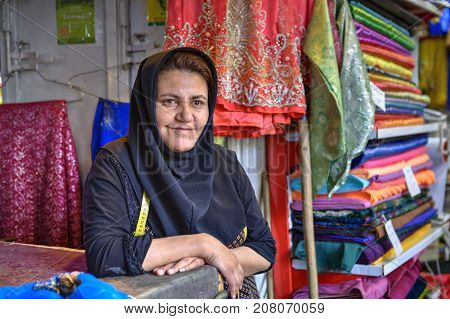 Fars Province Shiraz Iran - 19 april 2017: A portrait of an unknown mature Iranian woman dressed in a hijab selling colorful fabrics in a textile shop in the bazaar.