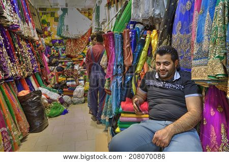 Fars Province Shiraz Iran - 19 april 2017: A mature Iranian male salesman relaxed sitting on a chair in a textile store waiting for buyers.