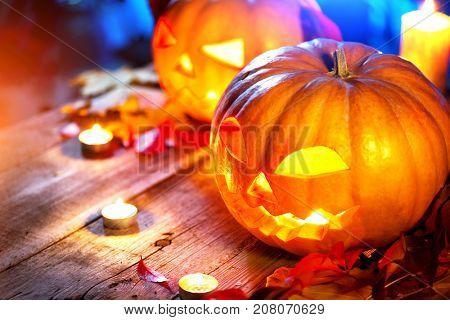 Halloween pumpkin head jack lantern with burning candles over wooden background. Halloween holidays art design, celebration. Carved Halloween Pumpkins with burning candles