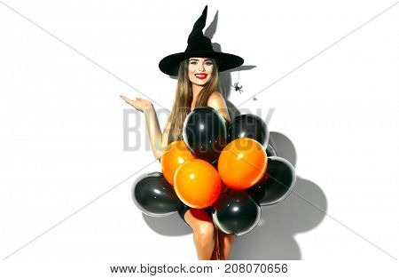 Halloween Party girl. Happy Halloween Sexy Witch holding black and orange Air balloons. Beautiful young surprised woman in witches hat and costume pointing hand, showing products, ads. Halloween art