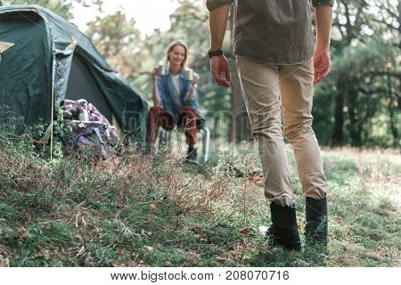 Low angle close up of male legs standing on grass while turning back to camera. Joyful woman is sitting near tent and holding two cups of tea prepared for them. Romantic rest concept