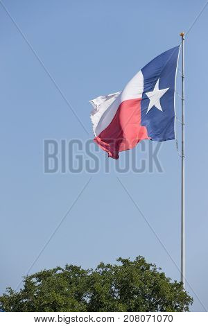 Texas flag waving against blue sky. State Flag of Texas on a Windy Day