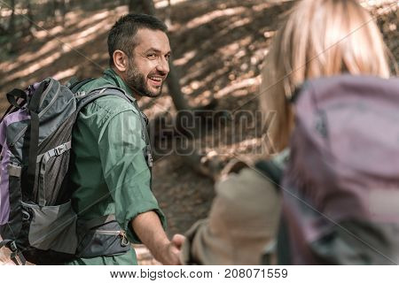 Come with me. Portrait of happy young man leading his girlfriend by hand and laughing. They are walking on pathway in the woods