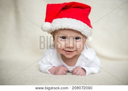 Little baby in red cap of Santa Claus celebrates Christmas. Christmas photo of infant in red cap. New Year's holidays and Christmas tree.