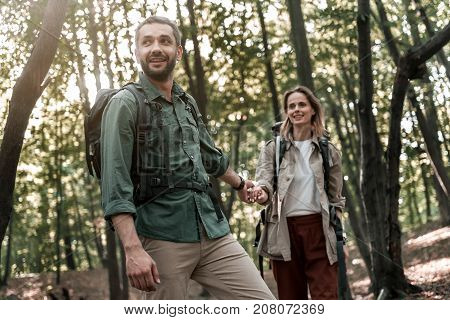 I want to show you my favorite place. Low angle of cheerful young man is holding female hand while leading her in the forest. They are carrying touristic backpacks and smiling