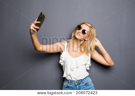 Happy Woman In Glasses With Beaming Smile Making Selfie On Gray