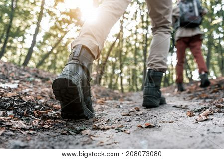 Low angle close up of male legs going on pathway in forest. Woman is walking in front of the man