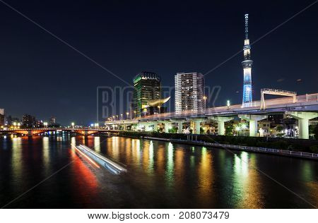 Skyline of Tokyo with skytree and river and lighttrails of boat at night, Tokyo, Japan