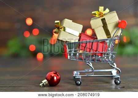Christmas shopping cart with Christmas gifts on wooden backgroud