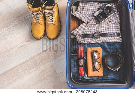 Camera and other accessories are locating on clothes in open suitcase. Boots near luggage at floor. Top view close up. Copy space on left side