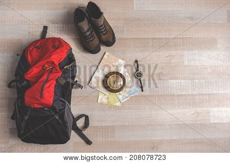 Convenient backpack is nearby boots on floor beside compass and maps. Top view close up. Nobody
