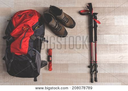 Red backpack is near boots and sticks for Nordic walking on floor in room. Top view close up. Nobody
