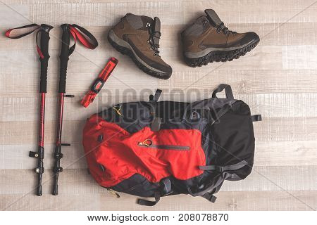 Red rucksack is near sticks for Nordic walking and convenient shoes on floor in room. Top view close up. Nobody