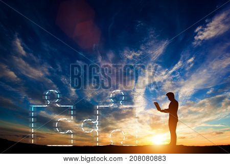 Man working on a laptop next to two puzzles being joined together. Concept of problem solving. 3d illustration.