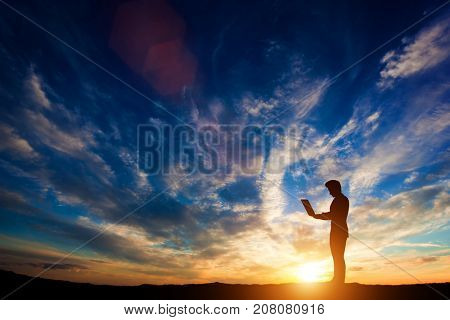 Man working on a laptop at sunset. Idea of work and career. 3d illustration.