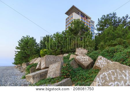 PITSUNDA ABKHAZIA SEPTEMBER 21 2017: Stone breakwaters with inscriptions of tourists from different cities on the beach in Pitsunda