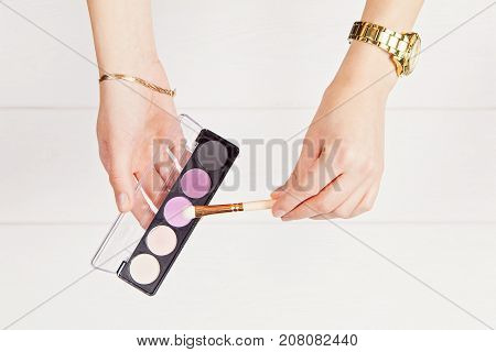 Flat lay with hands holding visage brush and eye shadows. Accessories and decorations on the white wooden background. Indoor