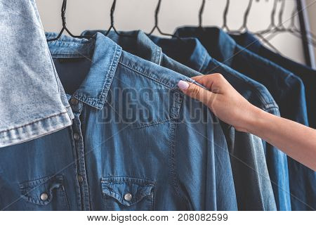 Girl is going to take jean shirt. Various jackets are on hangers. Close up of female hand taking thing. Copy space on left