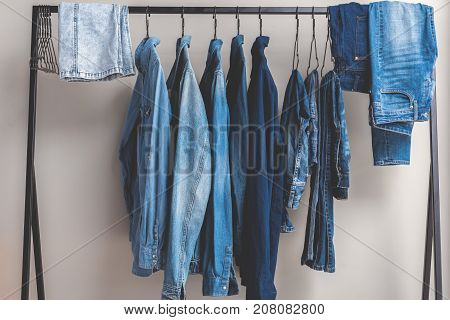 Various jean shirts and trousers are on hangers in wardrobe. Nobody. Close up