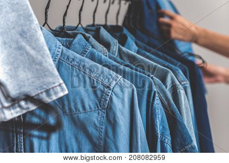 Man is going to take thing from rack. Close up of male hand taking jeans. Copy space on right side