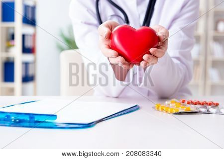 Doctor cardiologist with red heart in the hospital