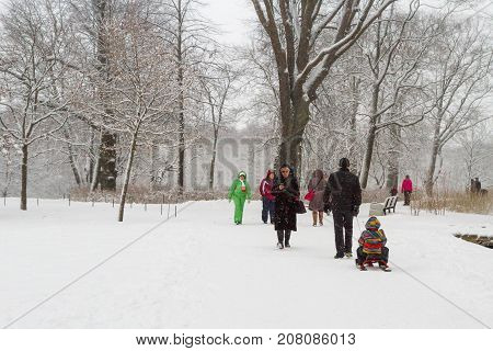 People Walk In Winter Park In The Snow