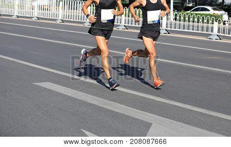 closeup of marathon runners running on city road