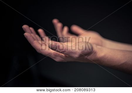 Caucasian man hands holding palms up and hands are empty. Shallow depth of field and focus.