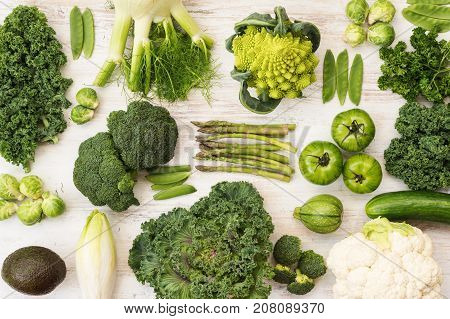Assortment of green vegetables on the white wooden table arranged in a grid, horizontal, top view, selective focus