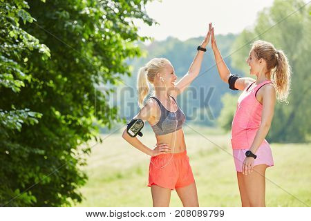 Two young women with motivational High Five happy to run together as friends