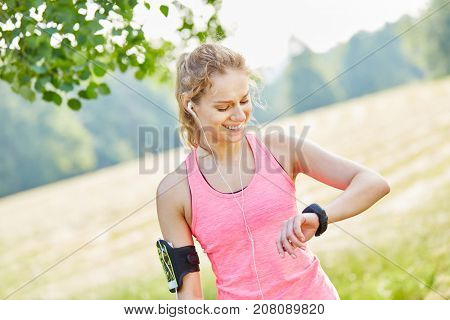 Woman as jogger checking health performance with smartwatch