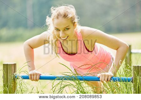 Young woman making push ups with power