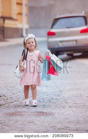 Girl Goes Shopping With Branded Packages Or Shopping Bags In City. Shopping With Child While Walking