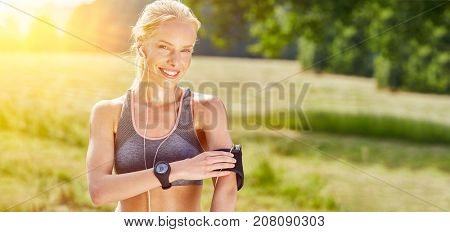 Young woman with wearable smartwatch and mp3 player in the nature