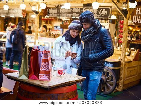 Young couple doing christmas shopping at christmas fair, using mobilephone.