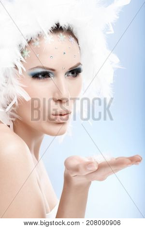 Beautiful woman in white feather cap and professional makeup makeup blowing a kiss in the air.