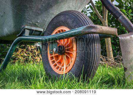 a wheelbarrow and a spade in the garden with grass