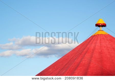 Red circus tent under the blue sky with beautiful clouds