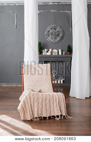 Wooden rocking chair with white soft back and plaid in a room with a good interior