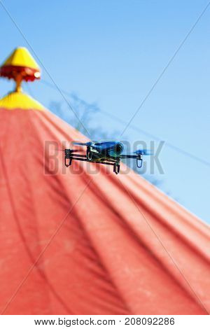 Blue drone flying over red circus tent against a blue sky in summer time and shoots a video