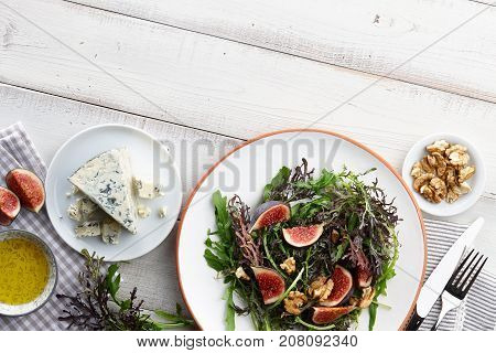 Salad with figs, blue cheese, arugula, mizuna and walnuts on white wooden background, top view