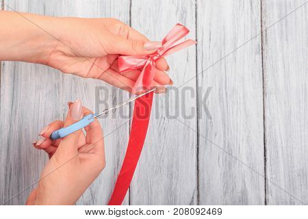 Hands with scissors, cut off a red ribbon. Close-up. On a gray background.