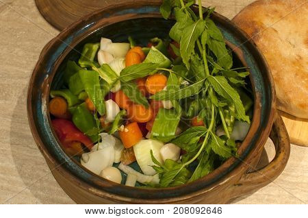 Freshly cut fresh vegetables intended for preparing stew dish cooked in clay pot in cooking oven
