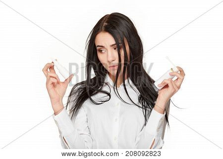 Studio portrait of sad brunette woman in shirt holding nasal spay and medicament in hands and posing. Concept of flu, illness, respiratory problems of health. Isolate on white.