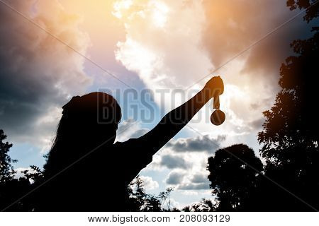 Blurred of silhouette hands raised and holding gold medals with ribbon against sunset background. to show team success in business Winners success award concept.