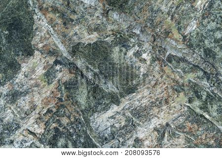 Surface of the gray granite stone with light lines and bands. There are brown spots and streaks. On granite there are bumps and pits. The structure of granite stone in cross section.