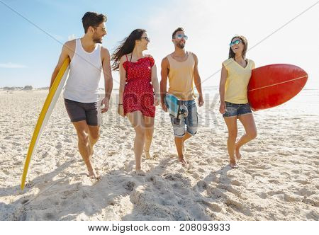 Friends walking together at the beach and holding surfboards